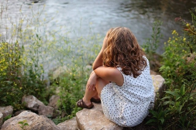 Stressed Woman Sitting by Lake