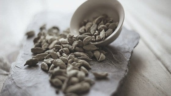 Cardamom spilled onto table runner from small bowl