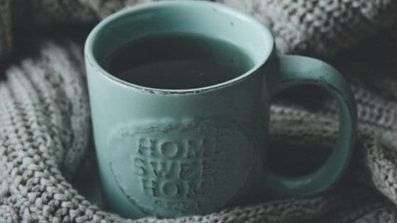 Teal blue coffee mug that says home sweet home surrounded by wool textile