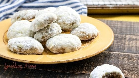 Yellow plate stacked with powdered sugar spice cookies